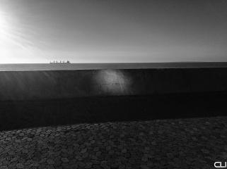 Reflected sun on sea wall.