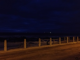 Streetlamps lit the foreground, ships on the horizon.