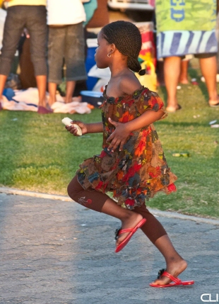 Girl running and dancing with her dad on the Sea Point beachfront, Cape Town, South Africa.