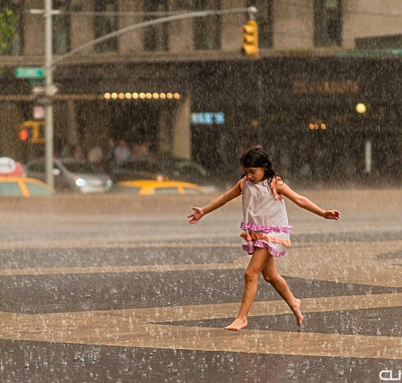 """In the midst of a sudden summer thunderstorm, this girl was 'dancing in the rain' at Lincoln Center while her mom (and the photographer!) stood under cover on the side of the plaza. What impressed me even more than the carefree joy of the child was her mom, who just stood and shared her happiness, encouraging her on... never a word about """"you'll get wet, how will we get your clothes dry... etc."""""""